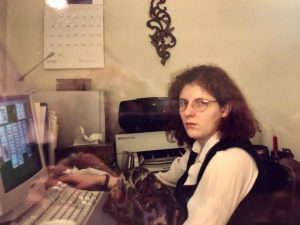 slightly scowling white person in their 20's with shoulder-length frizzy hair and a white shirt and black vest playing solitaire on a chunky CRT monitor with a boom box, printer, and beige computer tower in the background
